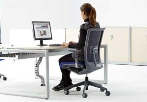 mujer sentada en una silla de oficina frente a un ordenador