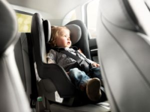 bebé sentado en la parte de atrás de un coche, en su sillita