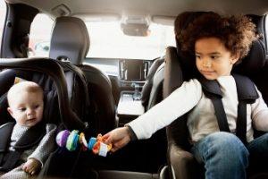 silla de coche a contramarcha bebé: dos hermanos detrás del coche
