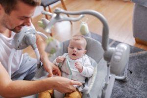 padre atendiendo a su bebé tumbado en la mecedora