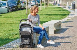madre sentada en un banco al lado de un carrito de Chicco plegado
