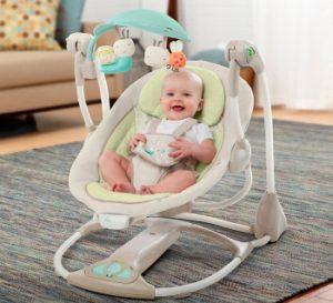 bebé riendo en su mecedora eléctrica con juguete