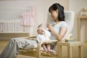 madre dandole el biberón a su bebé en una mecedora de lactancia
