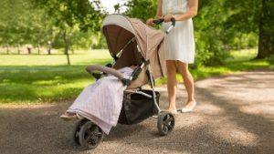 madre llevando una silla de paseo ligera por el parque