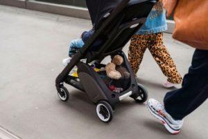 padres llevando a bebé en carrito